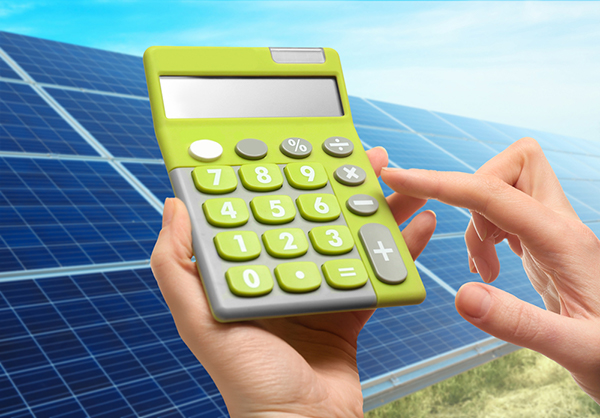Solar calculator held in a woman's hands in front of a view of solar panels