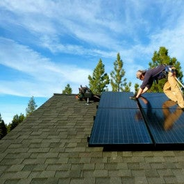 worker installing a solar panel on a home in Kentucky